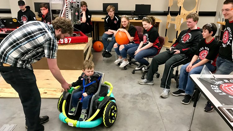 Tyler Jackson assists his son Cillian as Farmington High School Robotics Team members look on.