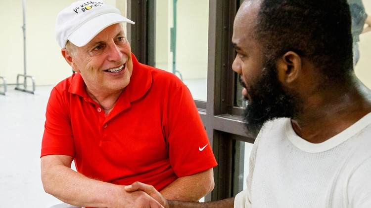 Pickleball instructor Roger BelAir (left) of Seattle greets inmate Clarence Dunner of Chicago during a pickleball match at the Cook County Jail.